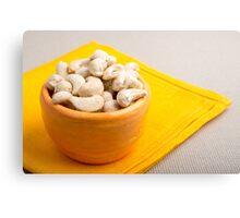 Raw cashew nuts in a small orange cup closeup Canvas Print