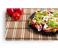 Closeup view fresh natural salad with raw tomato, cucumber, olives, onion, lettuce Canvas Print