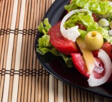 Closeup view fresh natural salad with raw tomato, cucumber, olives, onion, lettuce Sticker