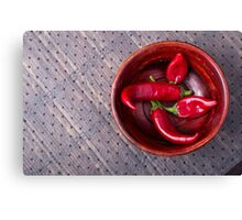 Top view of hot red chili peppers in a brown wooden bowl Canvas Print