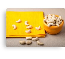 Selective focus on the tablecloth and raw cashew nuts closeup Canvas Print