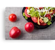 Close-Up top view fresh tomatoes and a part of a plate with vegetarian salad Canvas Print