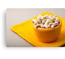 Selective focus on raw cashew nuts in a small orange cup Canvas Print