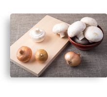 Raw champignon mushrooms and onions on the tabletop Canvas Print