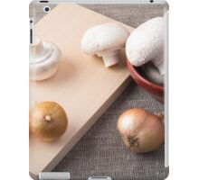 Raw champignon mushrooms and onions on the tabletop iPad Case/Skin
