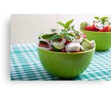 Green bowl with vegetable salad  on a green checkered tablecloth Canvas Print