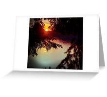 setting sun shining through the trees and reflecting off a northern lake Greeting Card
