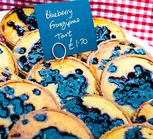 Delicious round blueberry tarts in British market by Stanciuc