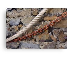 Rope and metal chain on grungy stone wall. Canvas Print