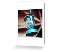 Old-fashioned blue lantern. Wooden background. Greeting Card