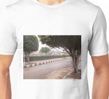 A narrow street running through a park with trees and a green hedge Unisex T-Shirt