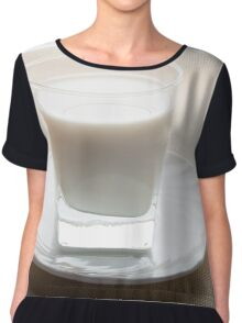 One glass of milk on a white saucer in backlit Chiffon Top