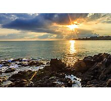 Menacing morning sea landscape with rocky coast and rising sun rays Photographic Print