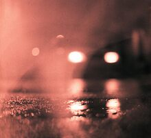 Analog photo of tarmac of street at night with car headlights in rain by edwardolive