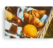 Picnic Basket With Orange Juice Bottle, Apples, Peaches, Oranges And Croissants On Green Grass In Spring Canvas Print