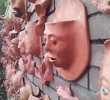 terracotta faces on brick wall by Rebecca York