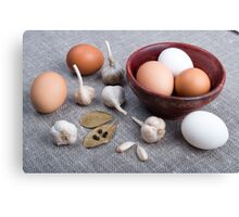 Raw eggs and garlic and spices on the kitchen table Canvas Print