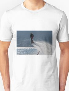 Flyboarder followed by spray over backlit sea T-Shirt