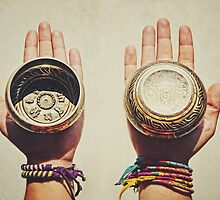 Two (2) hands holding decorated Tibetan Singing Bowls by Srdjan Kirtic