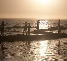 Children playing on the beach, silhouetted at dusk by lightwanderer
