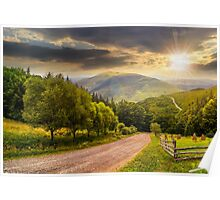 fence near road down the hill with  forest in mountains at sunset Poster