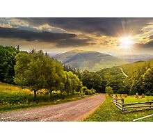 fence near road down the hill with  forest in mountains at sunset Photographic Print