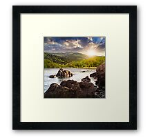 lake shore with stones near forest on mountain at sunset Framed Print