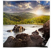 lake shore with stones near forest on mountain at sunset Poster