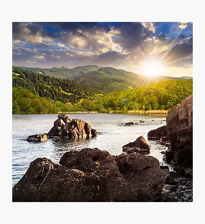 lake shore with stones near forest on mountain at sunset Photographic Print