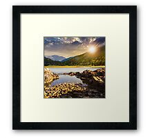 lake shore with stones near pine forest on mountain at sunset Framed Print