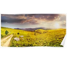 road on hillside meadow in mountain panorama at sunset Poster