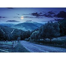 fence near road down the hill with  forest in mountains at night Photographic Print
