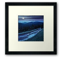 road through conifer forest in mountains at night Framed Print