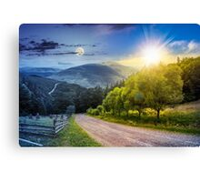 fence near road down the hill with  forest in mountains day and night Canvas Print