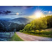 fence near road down the hill with  forest in mountains day and night Photographic Print