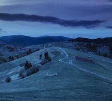 fence on hillside meadow in mountain at night Sticker