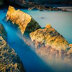 Rocks and misty blue ocean by Ralph Goldsmith