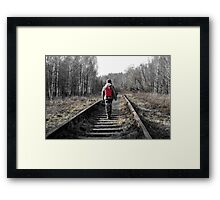 little boy goes deep into the forest along the rails Framed Print