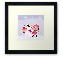 Happy smiling kids in winter costumes making snowman Framed Print
