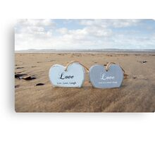 couple of inscribed wooden love hearts in the sand Canvas Print