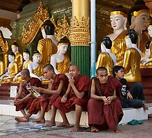faithful Buddhist monks sitting around Buddha Statues in SHWEDAGON PAGODA by travel4pictures