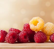 raspberry fruits in pile by Arletta Cwalina