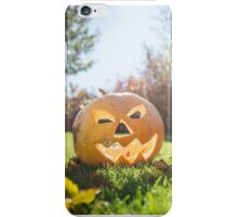 Halloween pumpkin on grass and leaves in the garden in nice sunny day iPhone Case/Skin
