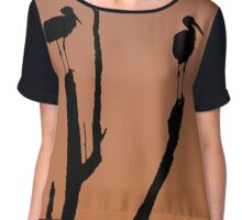 Silhouette of two storks standing on a tree at sunset.  Chiffon Top