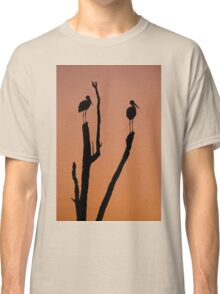 Silhouette of two storks standing on a tree at sunset.  Classic T-Shirt