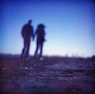 Romantic couple walking holding hands on beach in blue Medium format color negative film photo by edwardolive