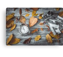 Autumn leaves camera and alarm clock on wooden table.Retro concept Canvas Print