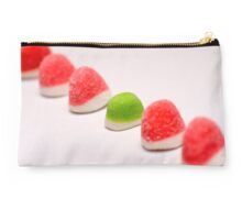 A line of red colourful sugared jelly sweets with one green one in the centre Studio Pouch