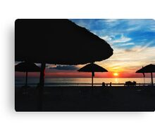 Sunset at the beach with sun umbrellas Canvas Print