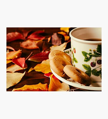 Closeup of cup of tea with biscuits and autumnal foliage Photographic Print
